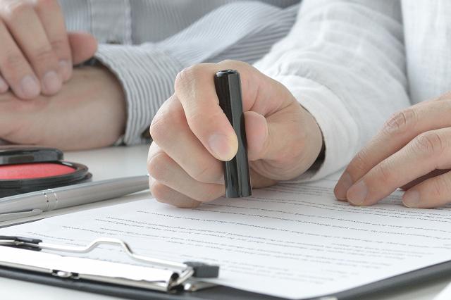 契約書に押印する人物の手